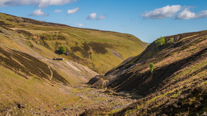 The remains of Bunton Mine with the Gunnerside Gill landscape, near Gunnerside, North Yorkshire, England, UK