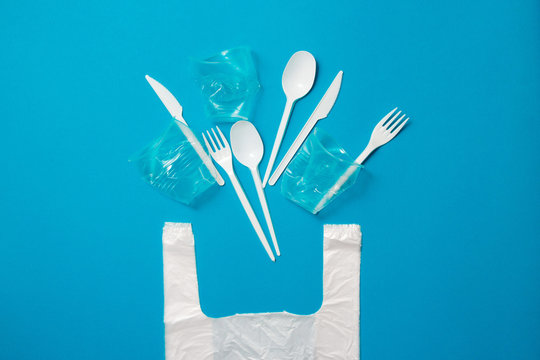 White single-use plastic knives, spoons, forks and bag on a blue background. Say no to single use plastic. Environmental, pollution concept.