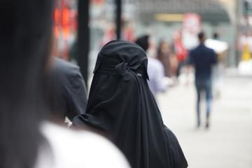 Fototapeta Rear View Of Woman In Hijab On Street
