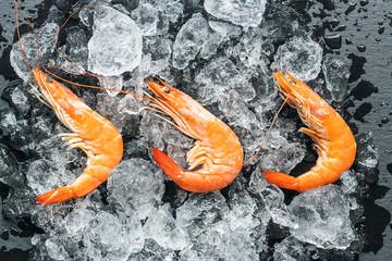 Three fresh prawns placed on ice and dark background