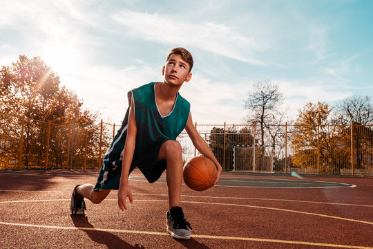 Sports and basketball. A young teenager in a green tracksuit playing basketball, leading the ball. Blue sky in the background and a sports ground in the background. Copy space