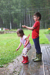 brother and sister play in rainy weather Children jump in puddle and mud in the rain.