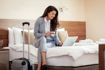 Young businesswoman working from hotel room on business trip, woman sitting on bed and using laptop.