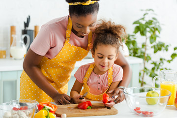 happy african american kid cutting bell pepper near mother in kitchen