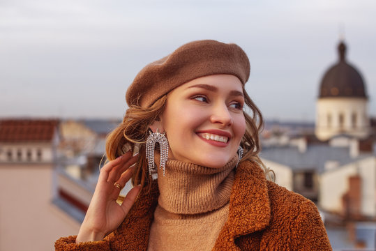Outdoor close up fashion portrait of elegant happy smiling woman wearing beige beret, turtleneck, brown coat, trendy big earrings with rhinestones, posing in European city. Copy, empty space for text