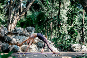 In de dag Ontspanning Begin to breathe. Full-length shot of caucasian woman standing in Wild Thing pose, Camatkarasana while practicing yoga outdoors, in a garden. Healthy lifestyle and relaxation concept