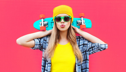 Portrait cool woman with skateboard wearing colorful yellow hat on pink background