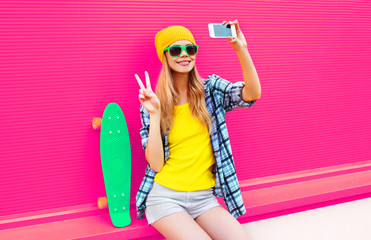 cool smiling woman taking selfie picture by smartphone with skateboard wearing colorful yellow hat on pink background