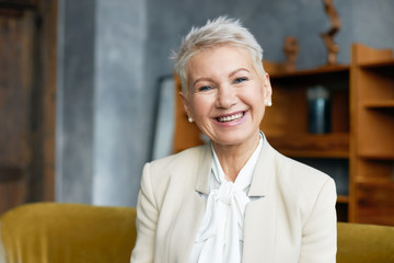 Portrait of experienced mature female professional with short pixie hairstyle and broad confident smile welcoming you in her office wearing elegant beige suit. Age, career and success concept