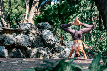 In de dag Ontspanning Transform your life. Full-length shot of caucasian woman standing in Headstand pose, Sirsasana while practicing yoga outdoors, in a garden. Healthy lifestyle and relaxation concept