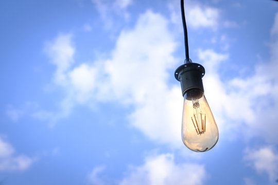 Low Angle View Of Illuminated Light Bulb Hanging Against Sky