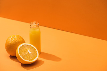 fresh juice in glass bottle near oranges on orange background