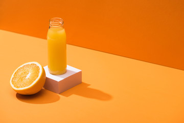 Poster Juice fresh juice in glass bottle near orange half and white cube on orange background