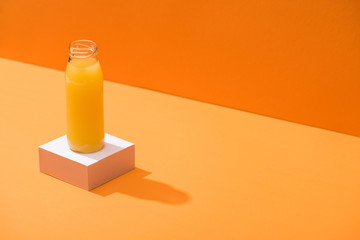 fresh juice in glass bottle on white cube on orange background