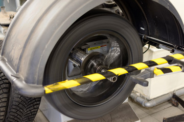 The car wheel rotates on the machine to balance the wheels. Tire fitting and wheel balancing.