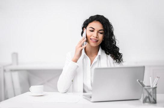 Smiling latin girl talking on the phone at coffee break