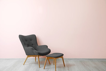 Stylish armchair near color wall in room