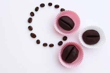 Homemade unbaked coffee bean cookies in white and pink paper cups, some pieces dipped in chocolate