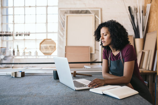 Female entrepreneur using a laptop in her framing shop