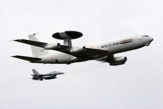 KLEINE BROGEL, BELGIUM - SEP 13, 2014: NATO Boeing E-3 Sentry AWACS radar plane in formation fligh with a Belgian Air Force F-18 over Kleine Brogel airbase.