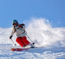 Aluminium Prints Winter sports Girl On the Ski. a skier in a bright suit and outfit with long pigtails on her head rides on the track with swirls of fresh snow. Active winter holidays, skiing downhill in sunny day. Woman skier