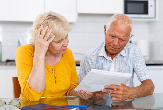Worried mature couple with documents disscusing in home