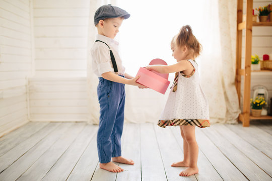 Boy and girl in the room on Valentine's day give a gift