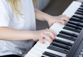 Child playing piano. Side view of a child playing piano. Close up on piano keys