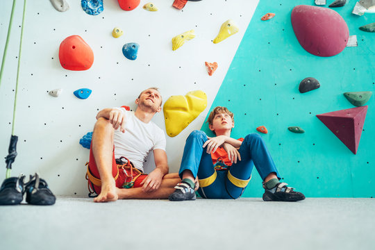 Father and teenage son sitting near the indoor climbing wall. They resting after the active climbing. Happy parenting concept image.