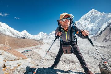 Fototapeta Portrait of smiling Hiker man with Nuptse 7861 m peak and Gorak shep settlement background with trekking poles, UV protecting sunglasses. He enjoying mountain during Everest Base Camp trekking route. obraz
