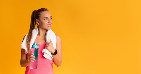 Sporty Woman With Bottle Of Water And Towel Wrapped Around Neck