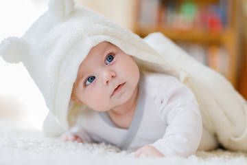 Baby girl wearing white towel or winter overal in white sunny bedroom