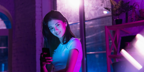 Smiling, looking forward. Cinematic portrait of stylish woman in neon lighted interior. Toned like cinema effects in purple-blue. Caucasian female model using smartphone in colorful lights indoors.