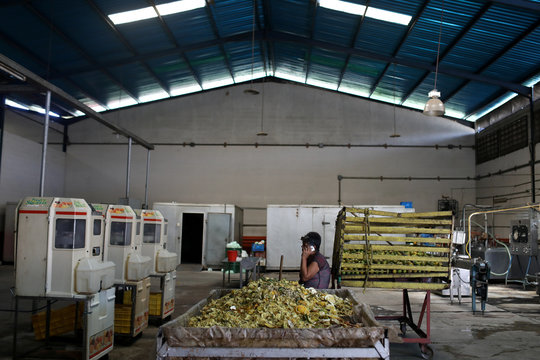 An employee talks on phone inside a non-operative orange juice factory in Bejuma