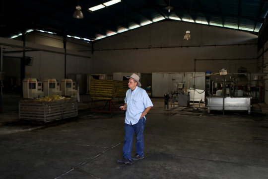 Venezuelan citrus farmer Martin Cabrera walks inside a non-operative orange juice factory in Bejuma