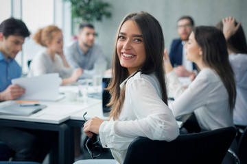 Positive secretary smiling to camera during meeting