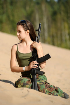 girl in the summer on a sandy slope with a gun