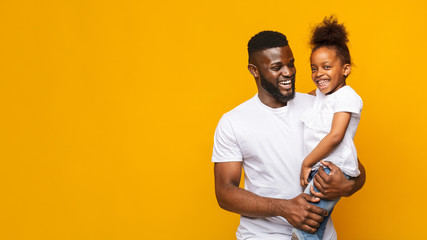 Happy african man holding little daughter over yellow background
