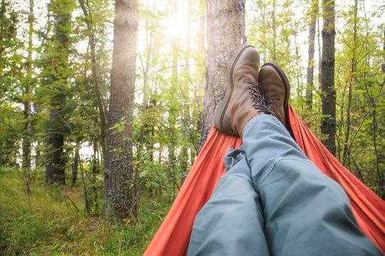 Man relaxing in camping hammock