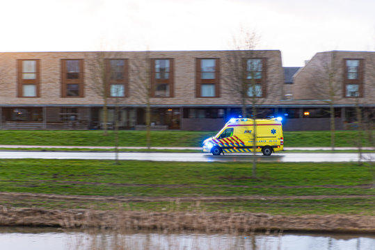 a dutch ambulance driving at high speed with flashing lights, blurred background. 28 Jan 2020 zeewolde flevoland the netherlands