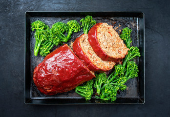 Traditional American meatloaf from ground beef with ketchup and broccoli as top view on a rustic metal tray with copy space