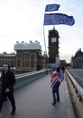 A man holds EU and Britain flag near the Houses of Parliament in London