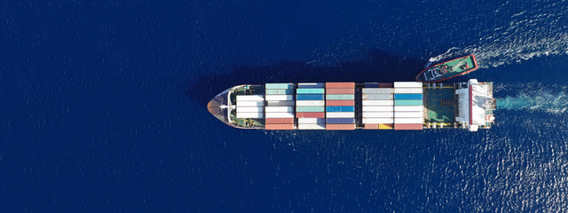 Aerial top down ultra wide photo of Container cargo Ship carrying load in truck-size colourful containers in deep blue open ocean sea  Wall mural