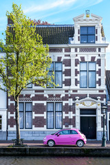 Street view of Leiden with a pink car in the foreground.