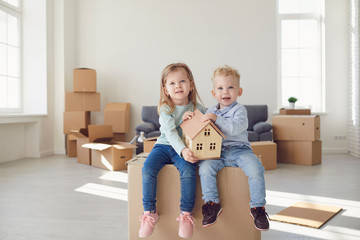 Two children are sitting on a box for moving they are holding a model of a house in a new bright room.