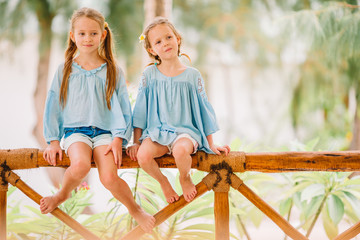 Little happy funny girls have a lot of fun at tropical beach playing together. Sunny day with rain...