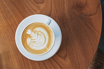 Fotobehang - A cup of coffee with latte art on the wooden table
