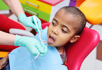 cute black baby boy African American smiling sitting in the dental chair at the examination at the...
