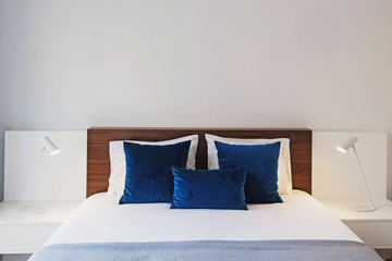 Modern bedroom with white walls and blue color decorative pillows