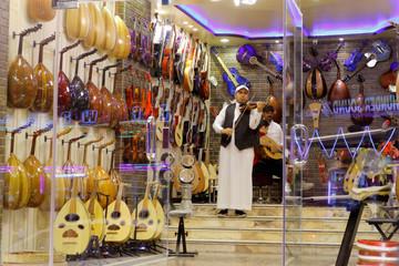 A Saudi violinist plays the violin at a musical instruments shop at the Hilla market, in Riyadh